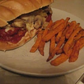 Meatball sub on a plate with sweet potato fries.