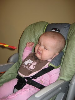 Unhappy baby being fed with a spoon in a high chair.