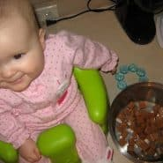 "Cute baby in a bumbo seat ""cooking"" in a kitchen."