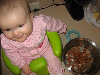 """Cute baby in a bumbo seat """"cooking"""" in a kitchen."""