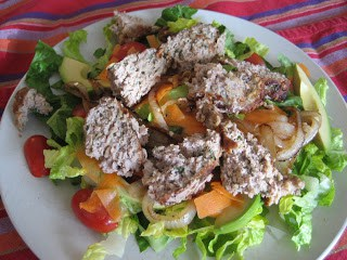 Turkey burger chopped up and placed on a green salad.
