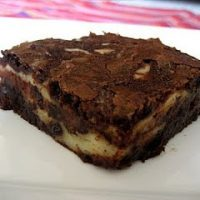 Brownie with cream cheese filling on a white plate.