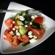 Triangle shaped bowl with tomatoes, feta, and cucumbers.