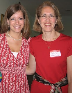 Two women with arms around each other, wearing red and smiling.