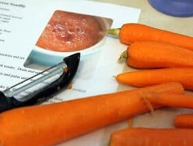 Carrots and peeler on a recipe.