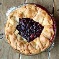 Overhead view of a rustic berry pie, crust pulled up around edges, berries showing in the middle, on a wooden background.