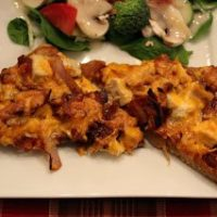Front view of two slices of BBQ chicken pizza on white plate, with salad in background.