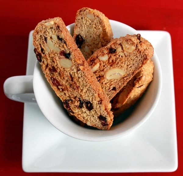 Top view of several biscotti, piled into white coffee mug, which is on square white plate. Background is red.