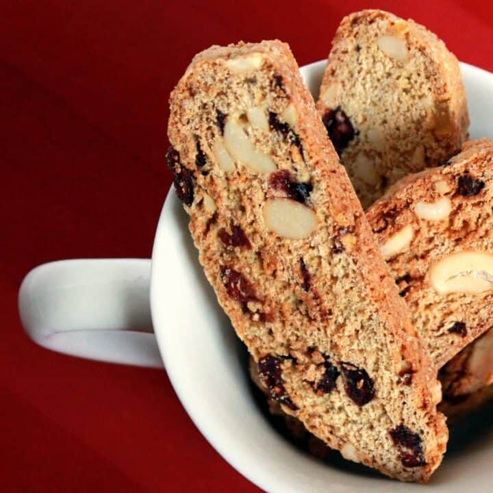 Biscotti flecked with nuts and cranberries, in a white teacup on a red background.