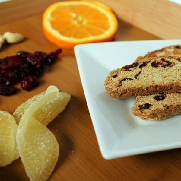 Partial image of 3 biscotti layered on white square plate. Plate is on bamboo cutting. board, along with 4 pieces of crystallized ginger, a handful of dried cranberries, a slice of orange and a few cashews.