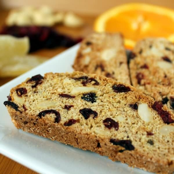 Close up image of one biscotti on white plate, with a couple more biscotti in back ground, along with orange slice, ginger, cranberries, and cashews.