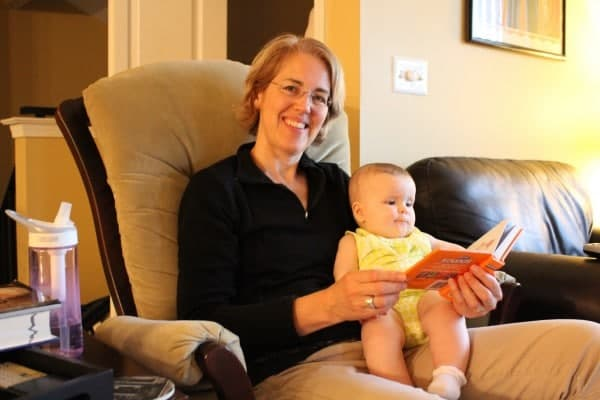 Image of author's mom and daughter, enjoying a book together, in a rocking chair.