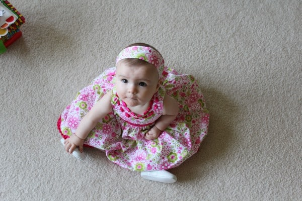 Sweet little girl in a pink dress sitting on white carpet and looking up at the camera.