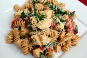Overhead view of a square white plate containing a mixture of rotini pasta, chicken, red peppers, and spinach, with sauce.
