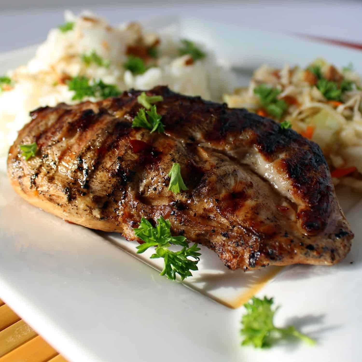 A grilled chicken breast on a white plate with coleslaw and rice in the background.