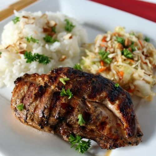 A white plate with a grilled chicken breast, coleslaw, and rice on it. Everything is sprinkled with fresh parsley.