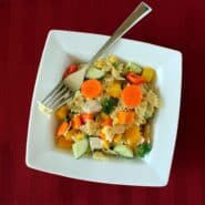 Close up view of pasta salad with farfalle pasta and carrots, corn, cucumber, chicken, and parsley.