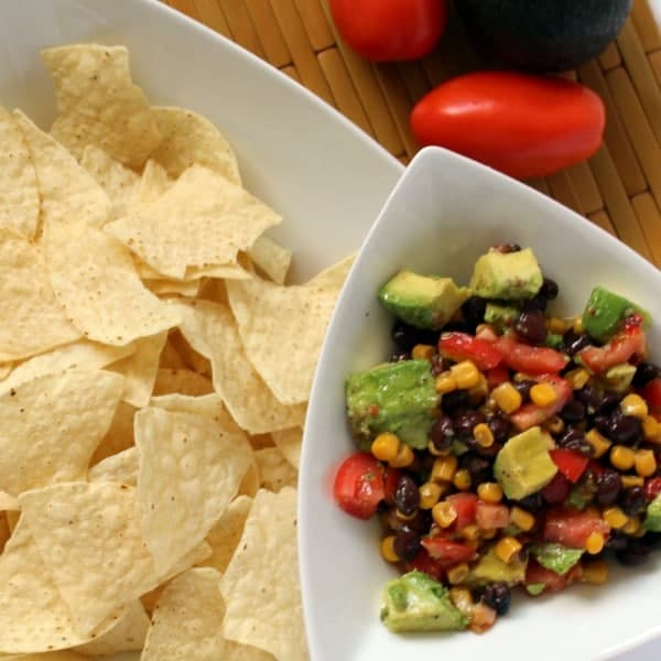 Overhead view of black bean dip in triangular white bowl, positioned over bowl of tortilla chips, roma tomatoes in background.