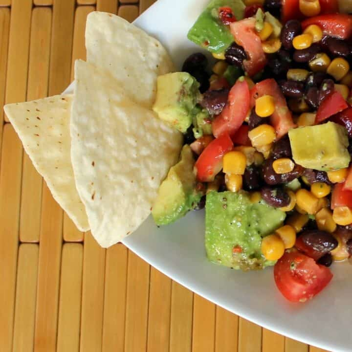 Beans, tomatoes, and avocados in a white triangle bowl with a couple of chips dipped into it.