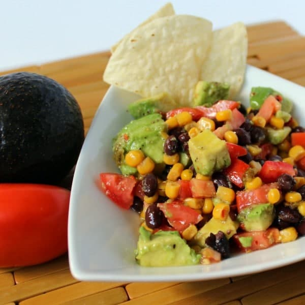 White triangular bowl of dip with two tortilla chips inserted into dip. Partial view of Roma tomatoe and avocado in background.