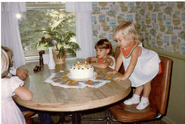 Young children at a table around a birthday cake.