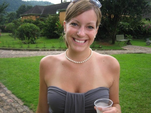A woman standing in a tropical location in a strapless shirt holding a beverage.