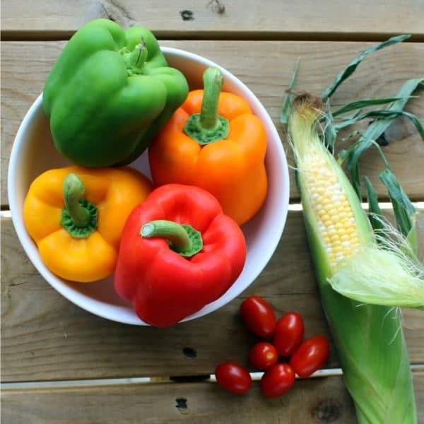 Fresh ingredients are on a wooden background; pictured are grape tomatoes, fresh corn in the husk, and a bowl of multicolored bell peppers.