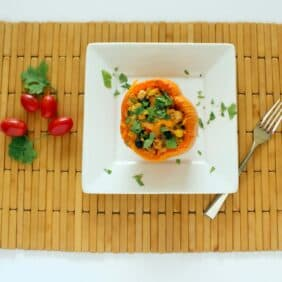 A stuffed bell pepper on a white plate, on a wooden placemat, sprinkled with fresh cilantro.