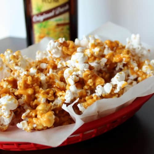 Caramel corn in a red basket with a bottle of rum in the background.
