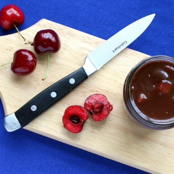 Overhead view of cutting board, with arrangement of jar containing sauce, a knife, and assorted cherries.