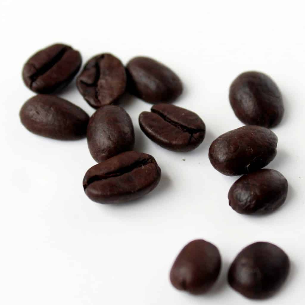 Close up of several whole coffee beans scattered on a white background