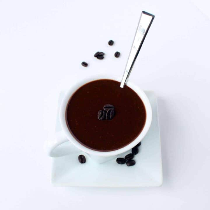 Overhead view of white mug and saucer containing mocha hot fudge and spoon, garnished with three coffee beans.