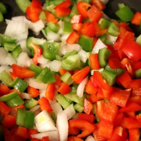 Close up of chopped red and green bell peppers, and white onion.