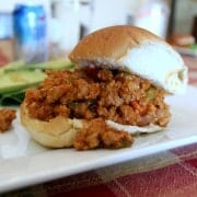 Messy sloppy joe sandwich on a white plate.