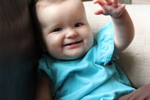 Image of same child, smiling and waving at camera.