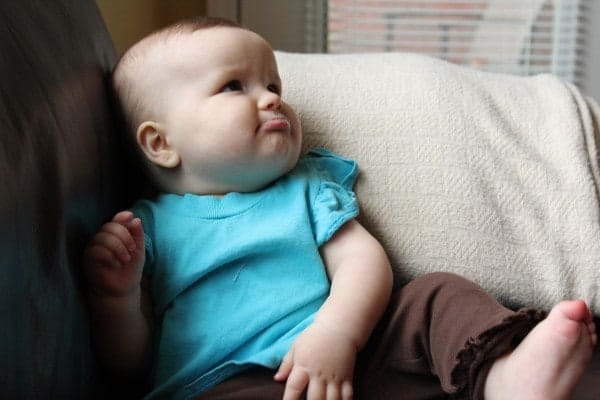 Image of same baby, sitting on couch, with a pout on her face. Child is wearing a short sleeved turquoise top, and long brown pants.