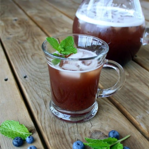 Overhead view of clear glass mug filled with blueberry iced tea, ice cubes, and a garnish of mint. Background of wooden deck boards.