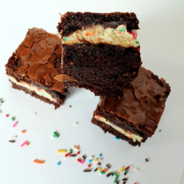 Overhead view of 3 brownies, the top brownie is on it's side to display the layers. Brownies are on a white surface with confetti sprinkles scattered.