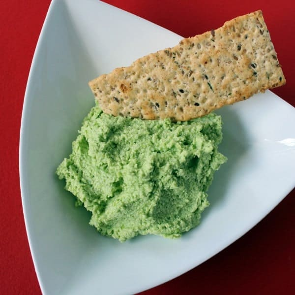 Bright green dip in a white triangular bowl with a cracker dipped into it.