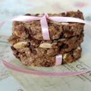 Three slices of brown chocolate biscotti, also with almonds, stacked and tied up with pink ribbon.