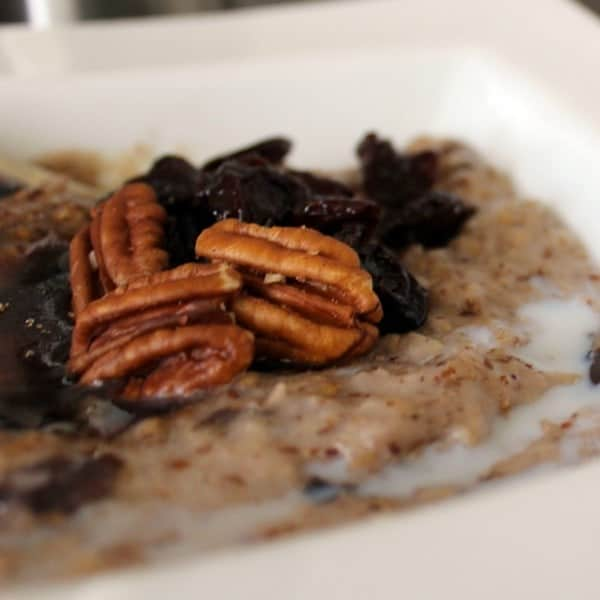 Close up view of oatmeal in a white bowl, topped with pecans, milk, dried cherries, and brown sugar.