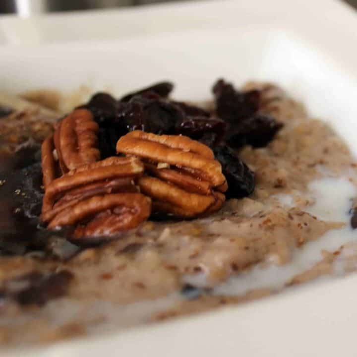 Close up view of oatmeal in a white bowl, topped with pecans, dried cherries, brown sugar, and milk.