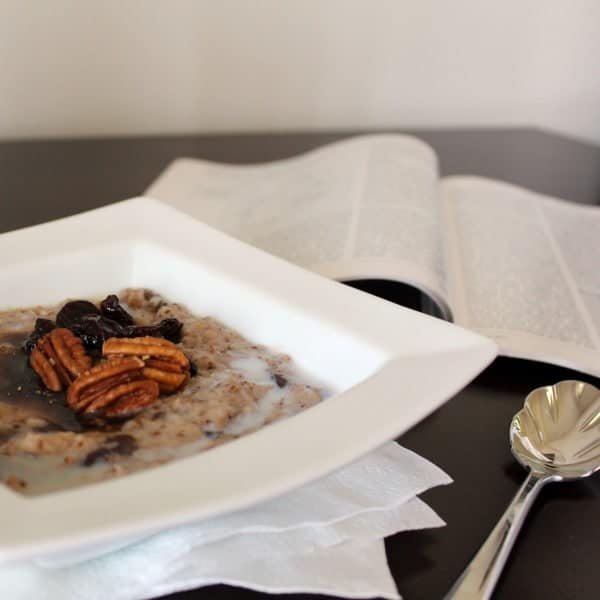 A white bowl filled with oatmeal with pecans and dried cherries on top. A open magazine, spoon, and napkins are also pictured.