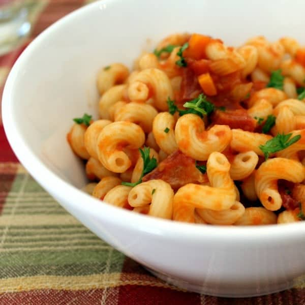 Close up of curly pasta in a tomato sauce with carrots and pancetta. It is sprinkled with fresh parsley.