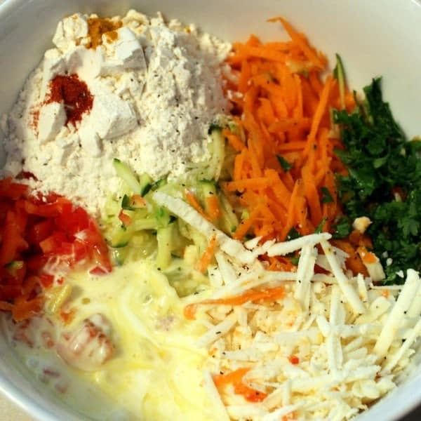 A bowl of vegetable pancake ingredients before they are mixed together: flour, turmeric, cayenne, shredded carrots, zucchini, feta cheese, eggs, cream, bell peppers, and parsley.