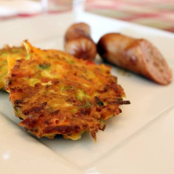 Zucchini and carrot fritters on a white plate with chicken sausage.