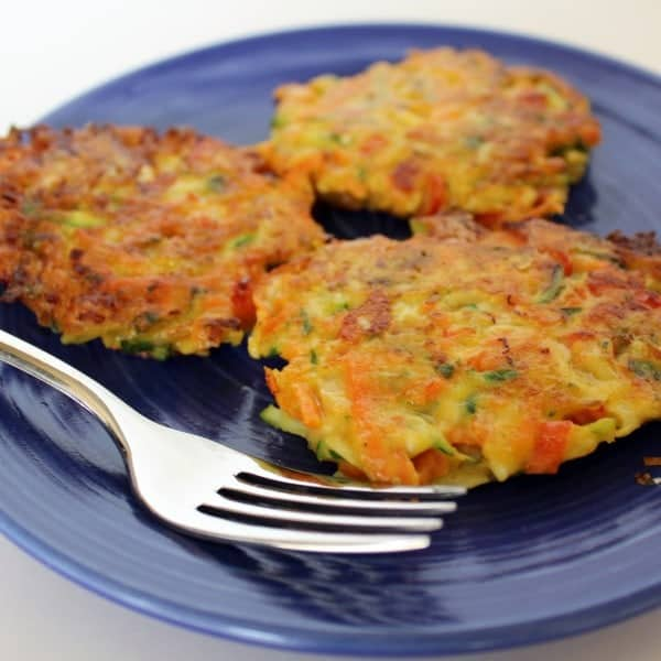 Three vegetable pancakes with zucchini, carrots, and red pepper visible. They are on a bright blue plate with a fork.