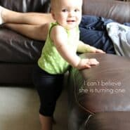 Small child standing up holding on to a brown couch.