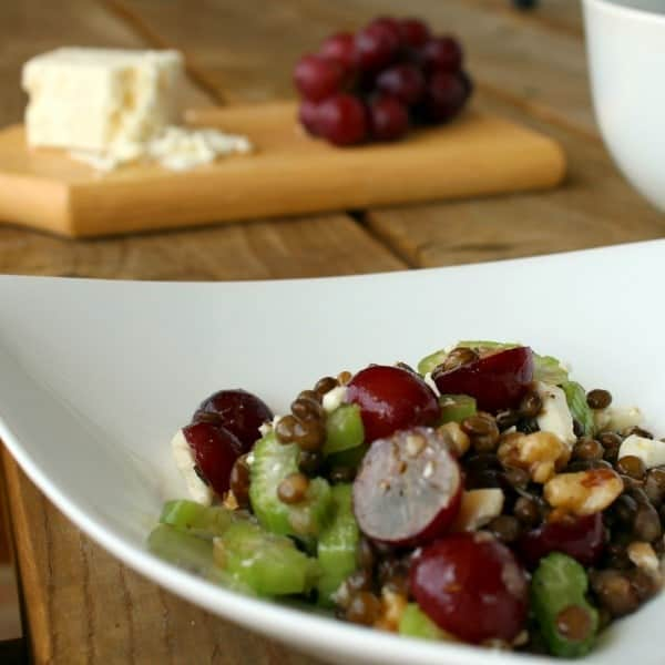 Close up view of a bowl of salad made with lentils, red grapes, celery, feta, and walnuts.