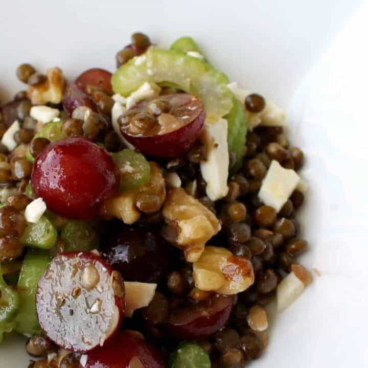 Close up view of lentils, red grapes, celery, walnuts, and feta. A shiny dressing is also visible.